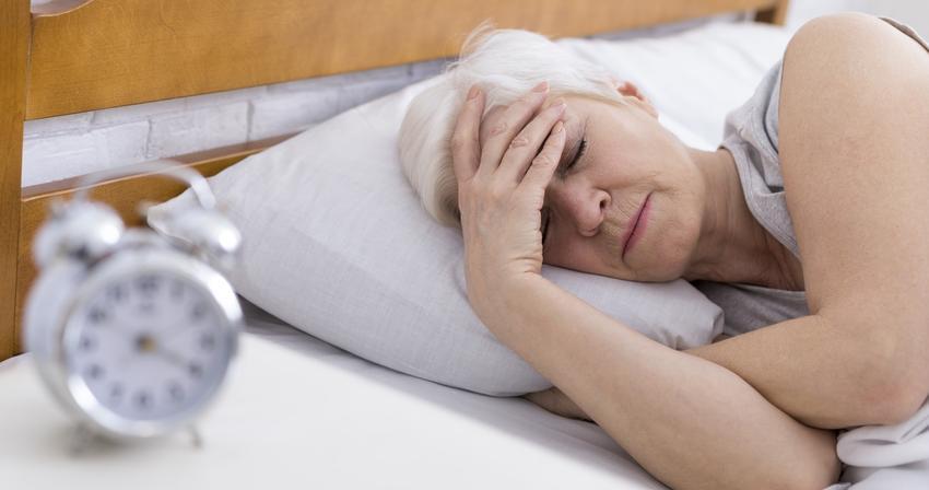 Zmęczona kobieta leżąca w łóżku oraz w jakim wieku pojawiają się pierwsze objawy menopauzy