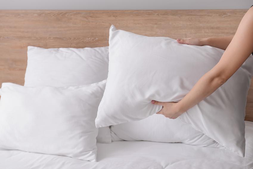 Kobieta poprawiająca wyprane poduszki na łóżku oraz porady jak wyprać poduszkę z pierza