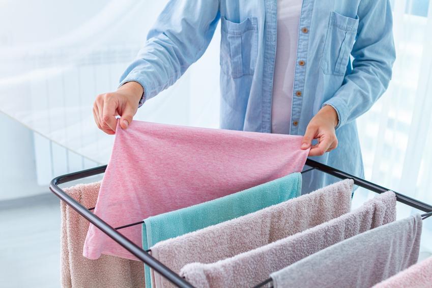 Kobieta wieszająca pranie na suszarce, a także polecana stojąca suszarka na pranie