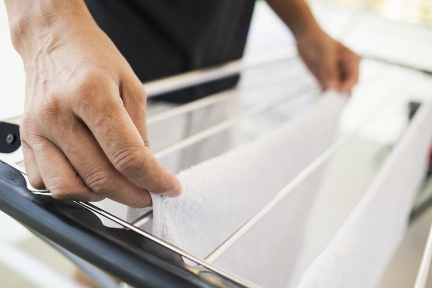 Mężczyzna wieszający pranie na suszarce, a także polecana rozsuwana suszarka na pranie