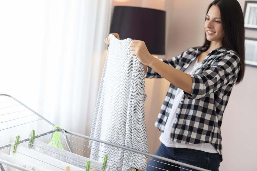 Kobieta wieszająca pranie na suszarce, a także polecana rozsuwana suszarka na pranie