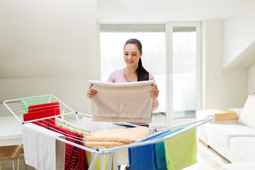 Kobieta wieszająca pranie na rozkładanej suszarce, a także suszarka na pranie vileda