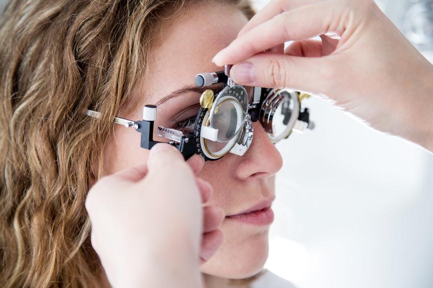 Kobieta podczas badania wady wzroku u okulisty oraz jak widzi astygmatyk