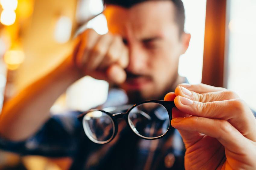Mężczyzna przecierający oczy po zdjęciu okularów oraz jak widzi astygmatyk