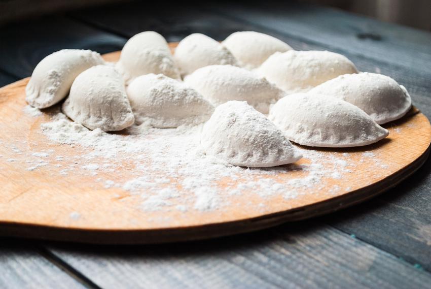Pierogi surowe na desce obsypane mąką oraz porady, jak mrozić pierogi