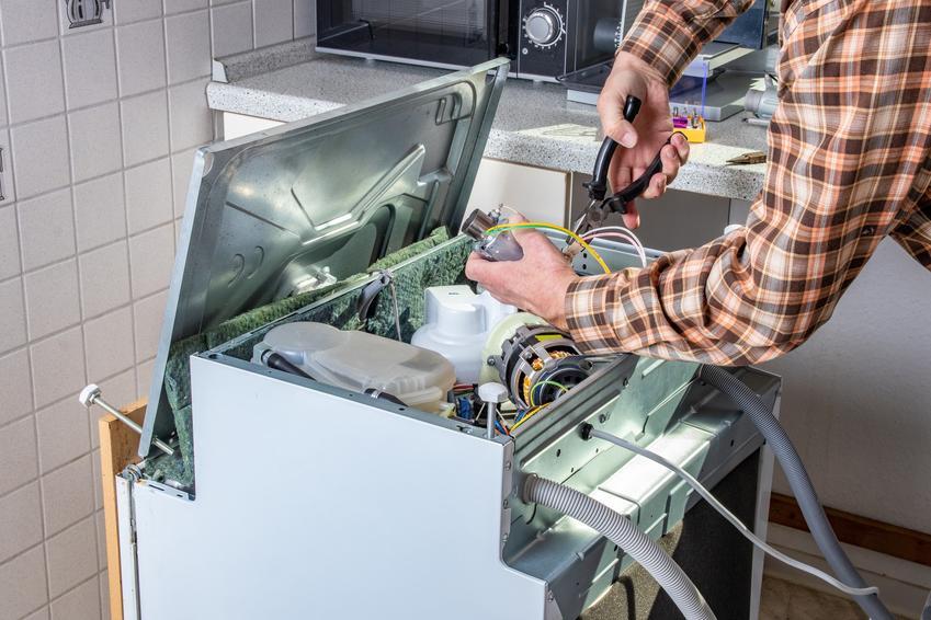Mężczyzna rozkręcający zmywarkę do naprawy oraz części do zmywarek bosch