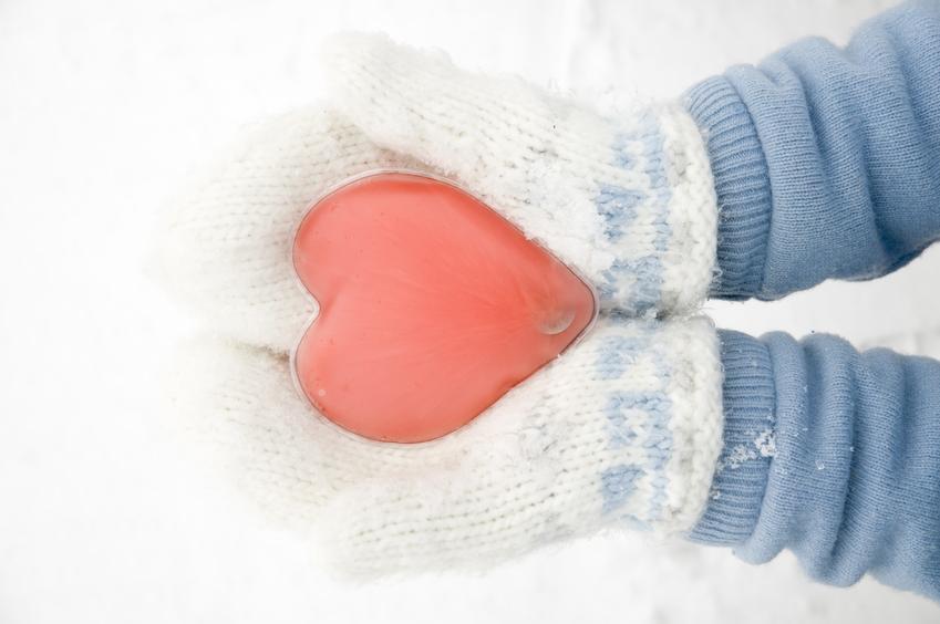 Kobieta trzymająca ogrzewacz do rąk w kształcie serca oraz inne ocieplacze na ręce