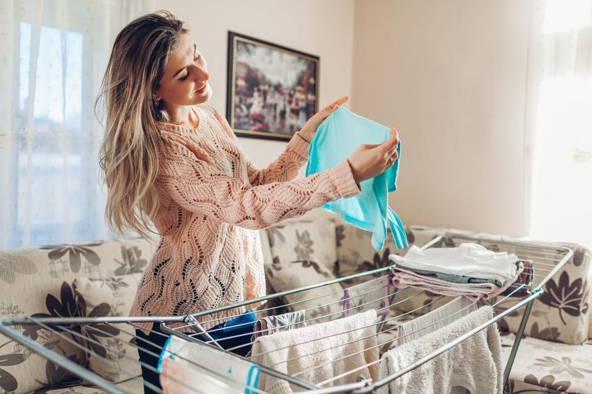 Kobieta wieszająca pranie na suszarce oraz polecana suszarka na pranie IKEA