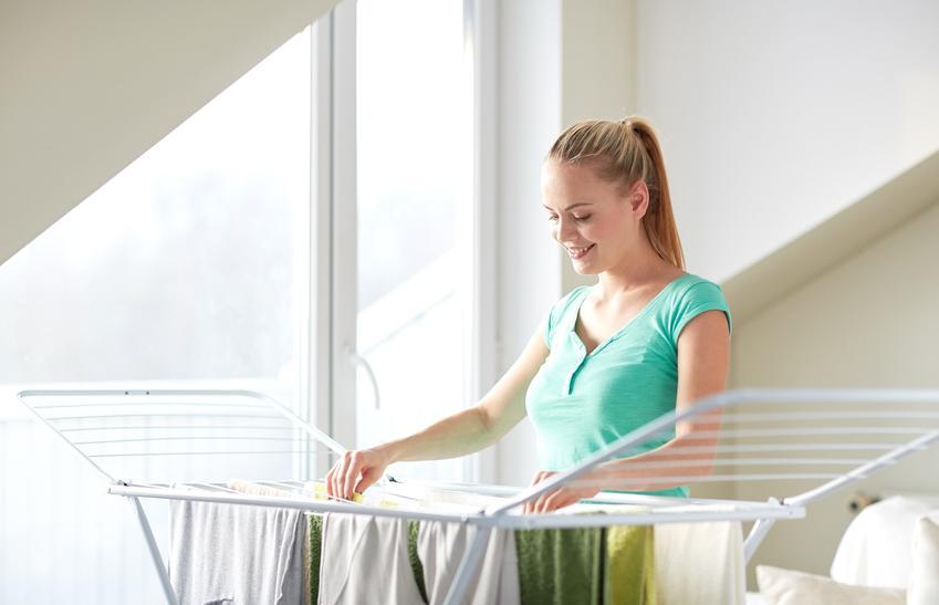 Kobieta wieszająca pranie na rozkładanej suszarce oraz suszarka na pranie leifheit