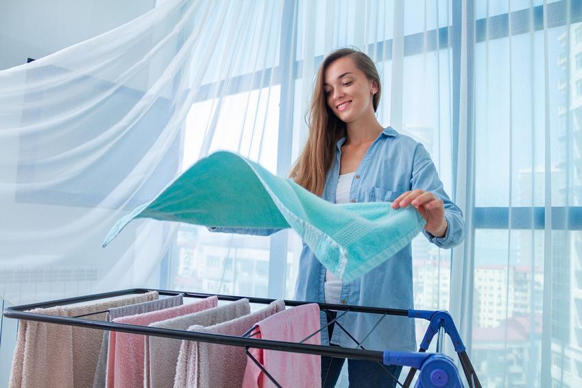 Kobieta wieszająca pranie na rozkładanej suszarce oraz suszarka na pranie w Castoramie