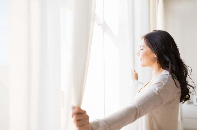 Kobieta rozsuwająca zasłony, czyli pranie zasłon krok po kroku, najlepsze sposoby i środki na pranie zasłon