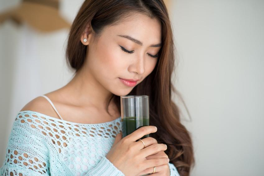 Kobieta pijąca zielony koktajl warzywny i porady jak oczyścić organizm ze złogów jelitowych