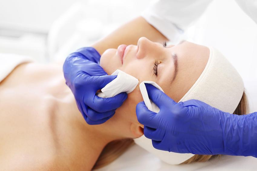 Kobieta podczas zabiegu oczyszczania u kosmetyczki, czyli jak usunąć zaskórniki