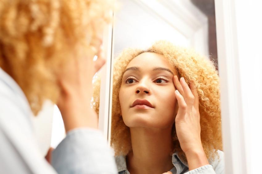 Kobieta oglądająca sobie twarz w lustrze oraz porady, jak usunąć zaskórniki