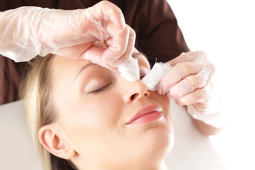 Kobieta usuwająca zaskórniki na nosie u kosmetyczki, czyli jak usunąć wągry z nosa