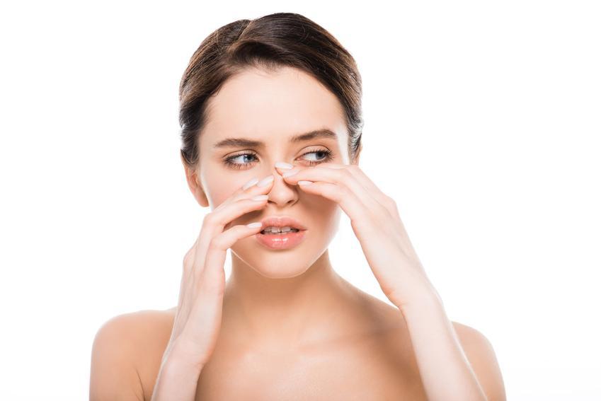 Kobieta zdegustowana wyglądem swojego nosa oraz zaskórniki na nosie
