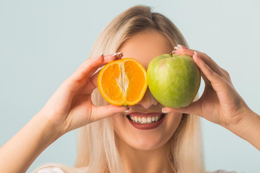 Uśmiechnięta kobieta trzymająca jabłko i pomarańczę oraz sposoby, jak zmniejszyć apetyt