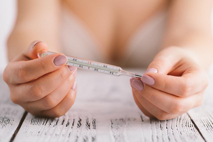 Kobieta sprawdzająca temperaturę ciała na termometrze, czyli jak rozpoznać owulację