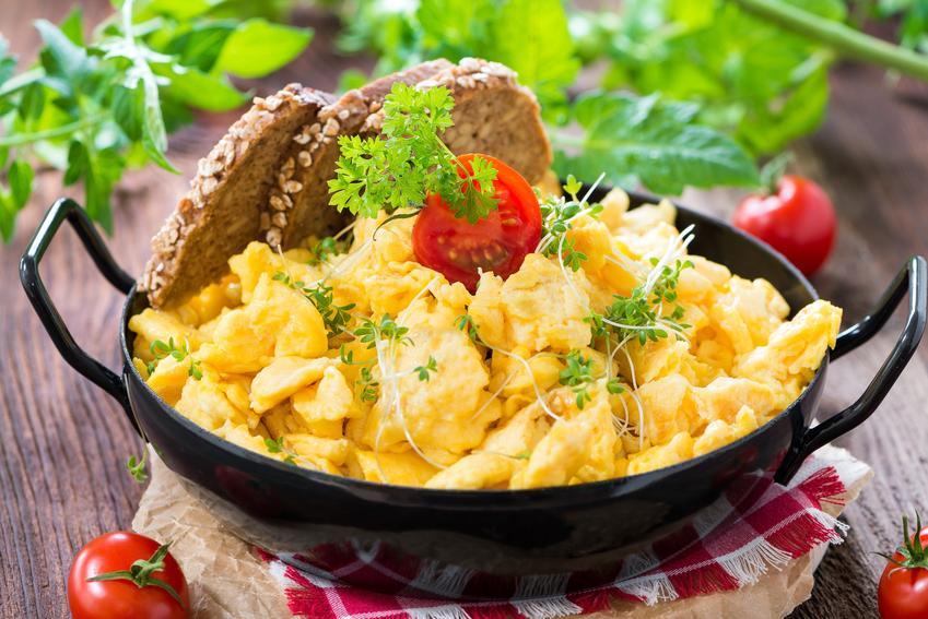 Jajecznica na maśle z ciemnym pieczywem i pomidorkiem oraz jak zrobić jajecznicę