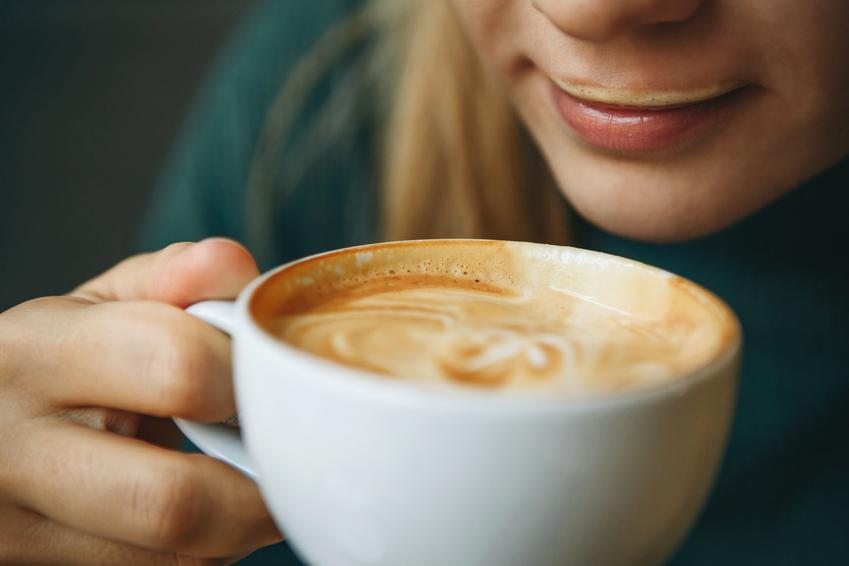 Kobieta pijąca kawę z pianką z filiżanki oraz porady, jak spienić mleko domowymi sposobami