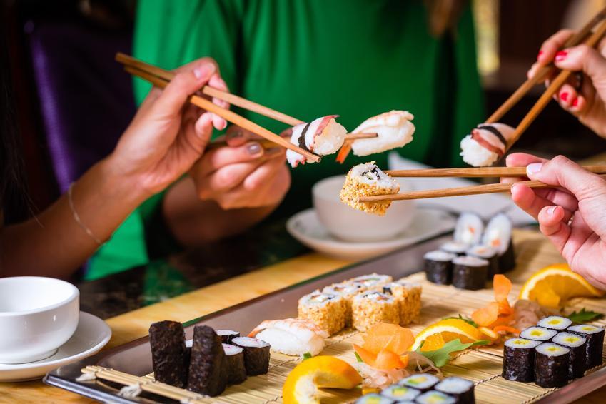 Spotkanie znajomych przy jedzeniu sushi i porady, jak trzymać pałeczki do sushi