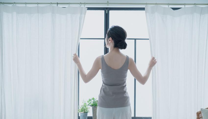 Kobieta w oknie poprawiająca firanę, a także upinanie firan i jak upiąć firnaki