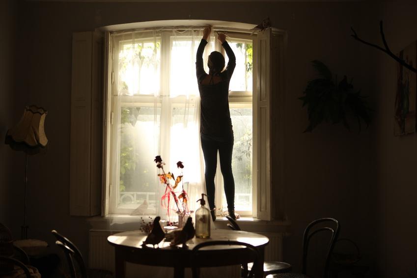 Kobieta podczas upięcia firan w oknie, a także najlepsze porady, jak upiąć firanki