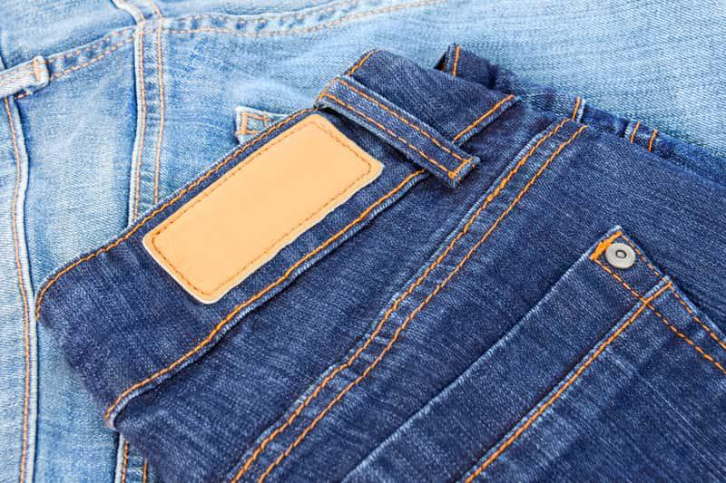 Złożone jeansy na stole, a także informacje, jak prać jeansy krok po kroku, sposoby, środki piorące, jak prać jeansy, żeby nie farbowały