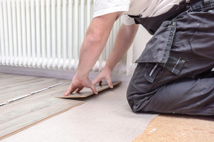 Męczyzna podczas układania paneli podłogowych, a także porady, jak kłaść panele podłogowe krok po kroku