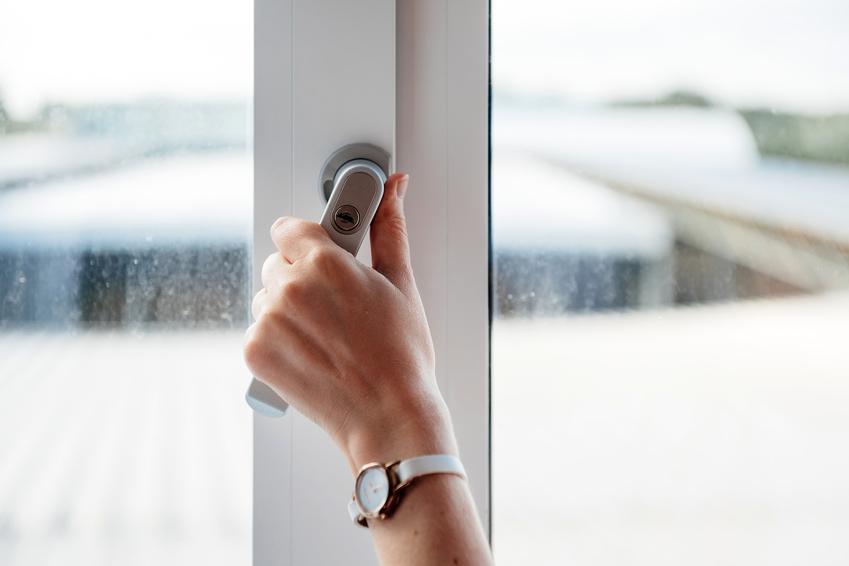 Kobieta trzymająca dłoń na klamce okna, a także porady, jak wyregulować okno