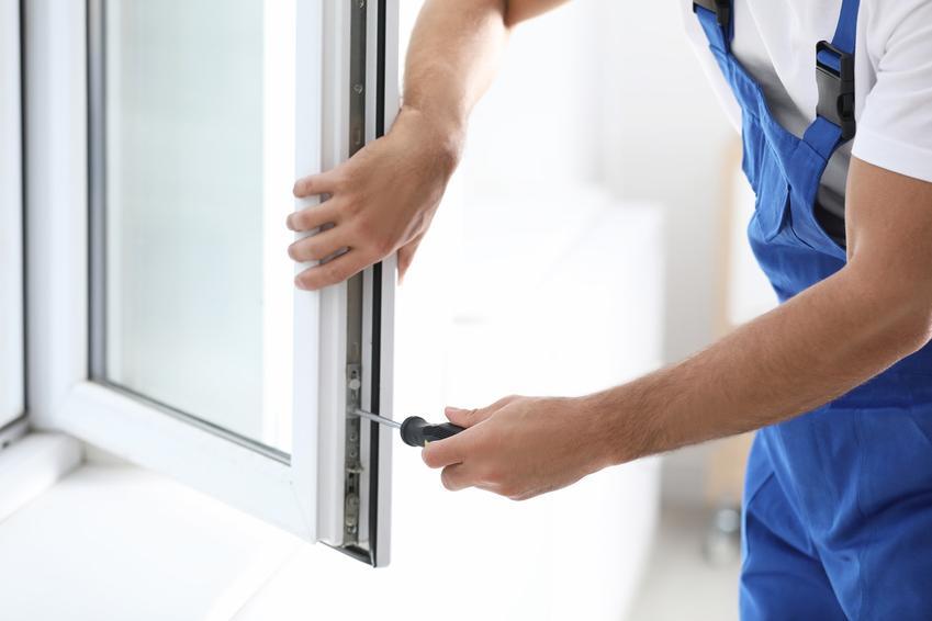 Mężczyzna podczas regulacji okna, a także porady jak wyregulować okno i regulacja okien plastikowych