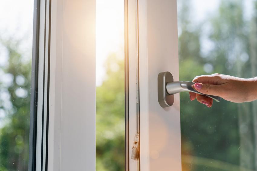 Dłoń na klamce okiennej, a także instrukcja regulacji docisku okien pcv i jak wyregulować okno