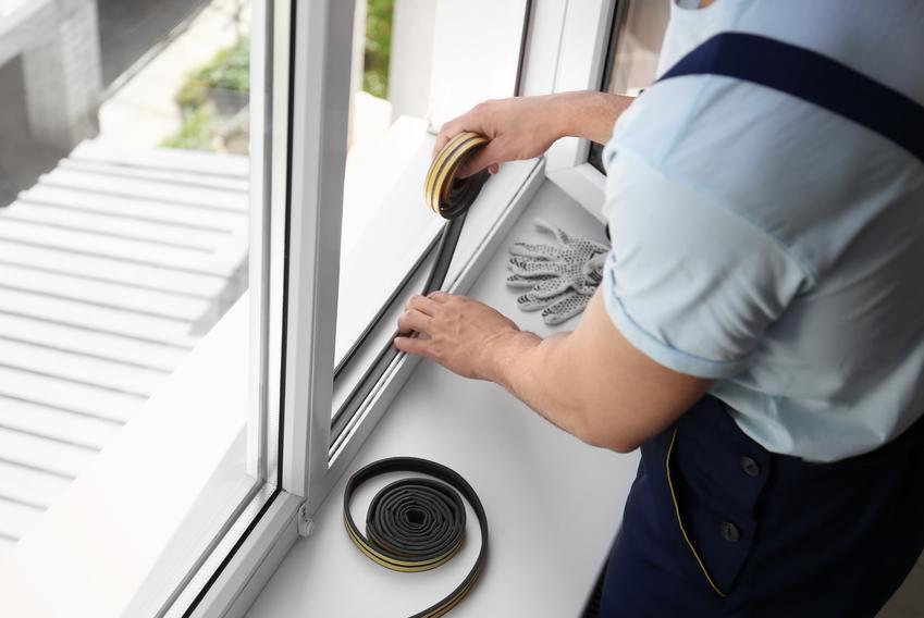 Uszczelnianie okien przez mężczyznę na zimę, czyli jak i czym uszczelnić okna