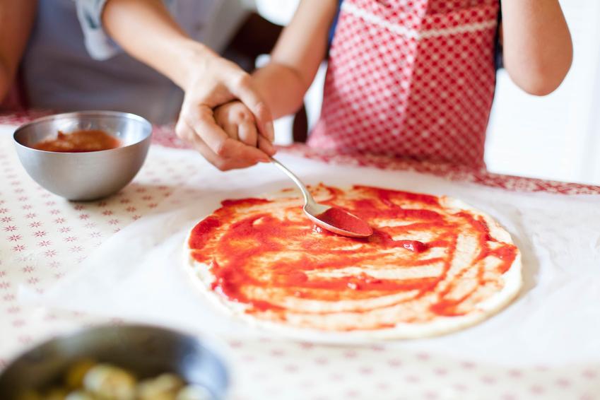 Domowa pizza z rozsmarowanym sosem pomidorowym oraz porady, jak zrobić pizzę