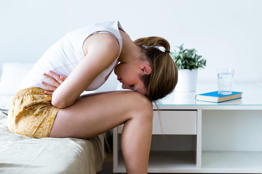Kobieta zwijająca się z bólu, a także informacje, gdzie boli wyrostek, jak boli wyrostek