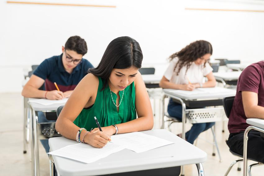 Młodzież szkolna pisząca wypracowanie, a także jak napisać rozprawkę