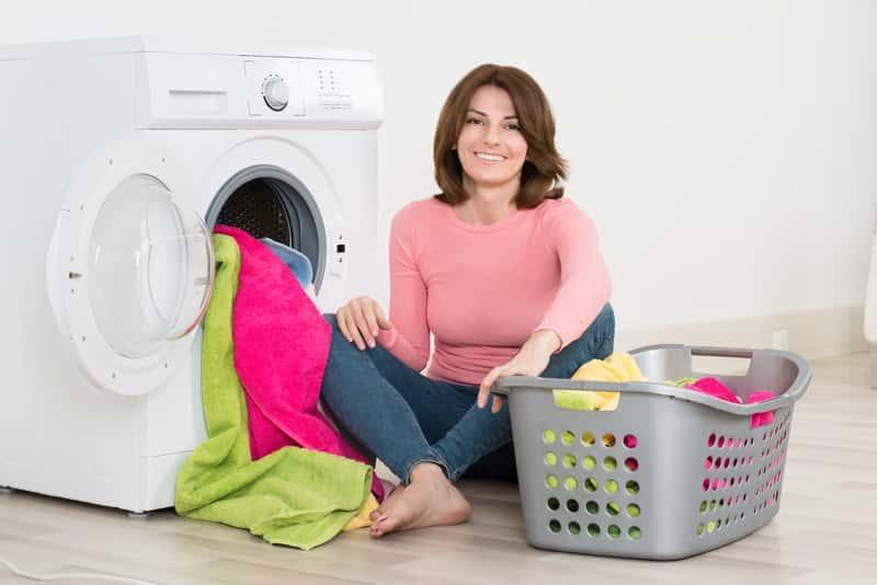 Kobieta wyciągająca z pralki pranie wyprane w płynie do prania Ariel, a także płyn Ariel, ceny, opinie, zastosowanie