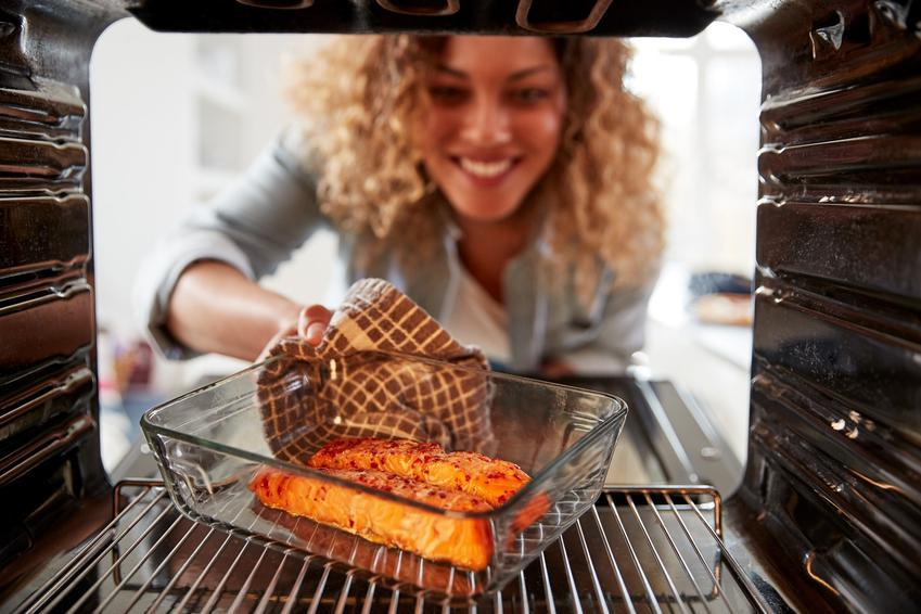 Uśmiechnięta kobieta i ryba w piekarniku, a także jak przygotowac rybę w piekarniku