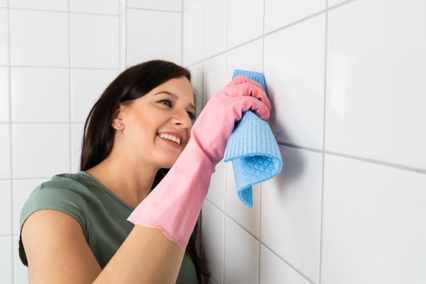 Kobieta podczas czyszczenia fug, a także porady jak wyczyścić fugi w płytkach