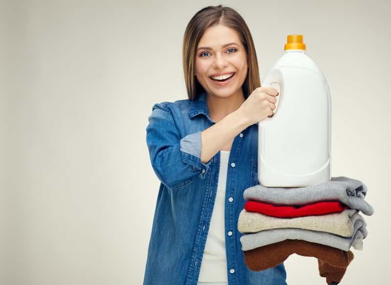 Kobieta trzymająca stos welnianych swetrów i płyn do prania, a także informacje, jak powinno wyglądać pranie wełny krok po kroku