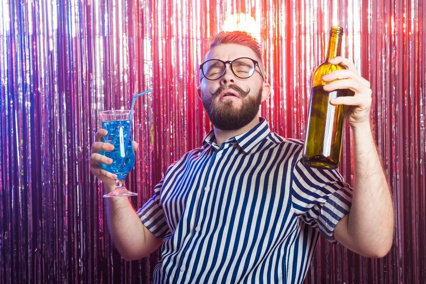 Mężczyzna z alkoholem na imprezie oraz sposoby, jak szybko wytrzeźwieć po alkoholu