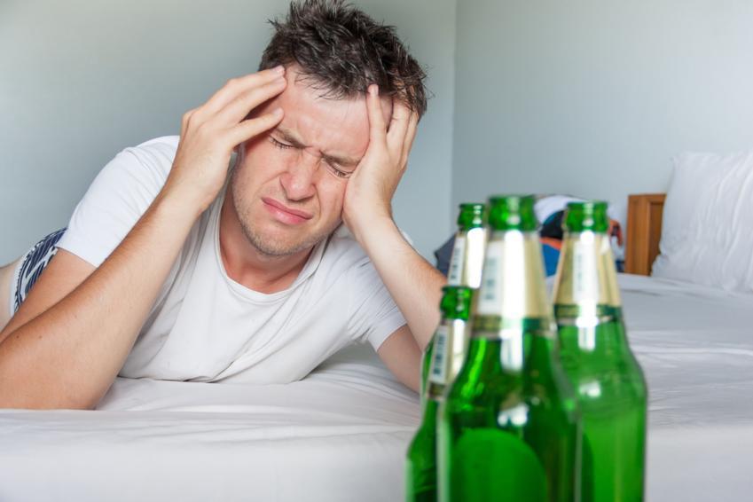 Mężczyzna na kacu przy butelkach po piwie oraz sposoby jak szybko wytrzeźwieć po imprezie