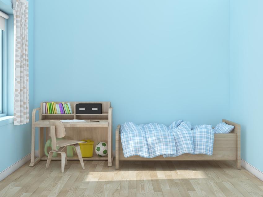 Łóżko w pokoju dziecięcym na tle niebieskiej ściany, a także polecane łóżko rosnące z dzieckiem i cena