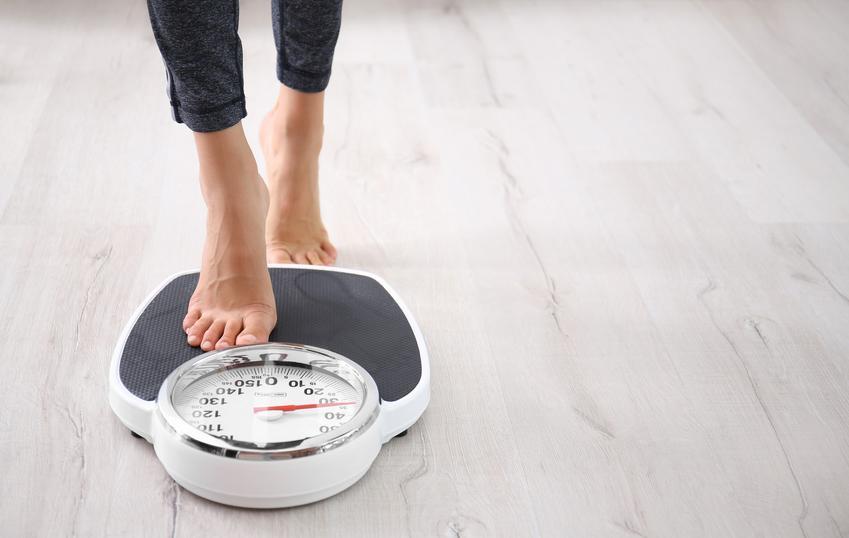 Kobieta wchodząca na wagę, a także porady jak przytyć i dieta na przytycie