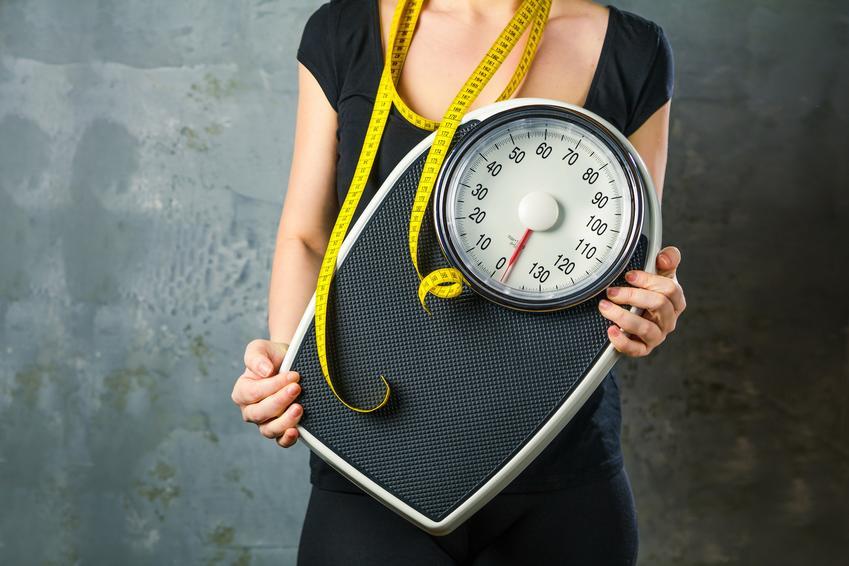 Kobieta trzymająca miarkę i wagę, a także porady jak przytyć i dieta na przytycie