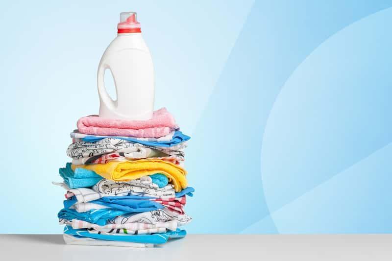 Stos prania z butelką płynu Perwoll, a także opinie o płynie do prania, najważniejsze informacje, zapachy, działanie, cena