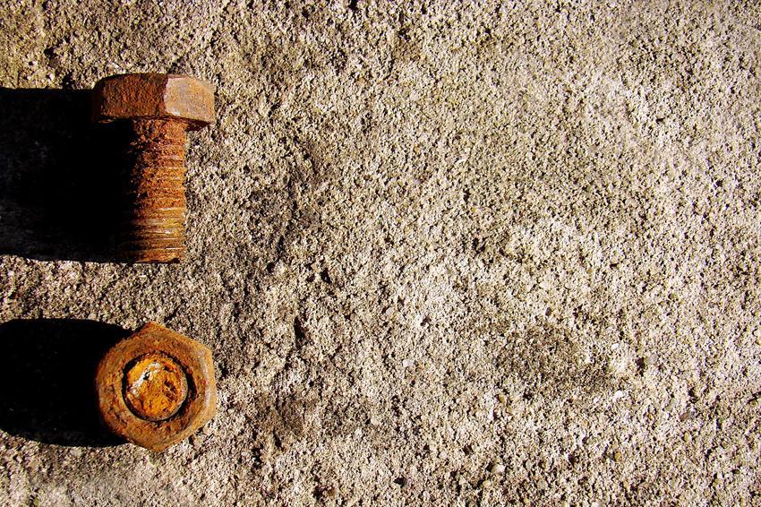 Zardzewiała i stara śruba na betonie, a także zapieczona śruba i jak odkręcić zapieczoną śrubę
