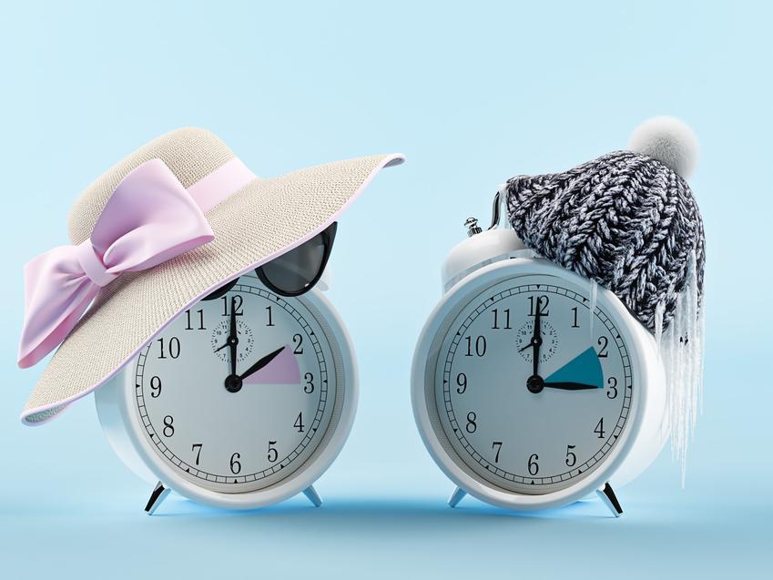 Dwa zegarki na niebieskim tle oraz zmiana czasu na zimowy i na letni w Polsce