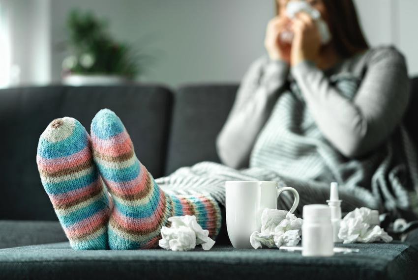 Chora kobieta w kolorowych skarpetkach, a także ile trwa grypa, w tym grypa żołądkowa