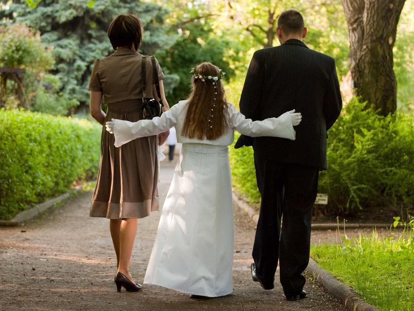 Dziewczynka komunijna z rodzicami, a także jak się ubrać na komunię, jeśli jesteś rodzicem lub chrzestnym
